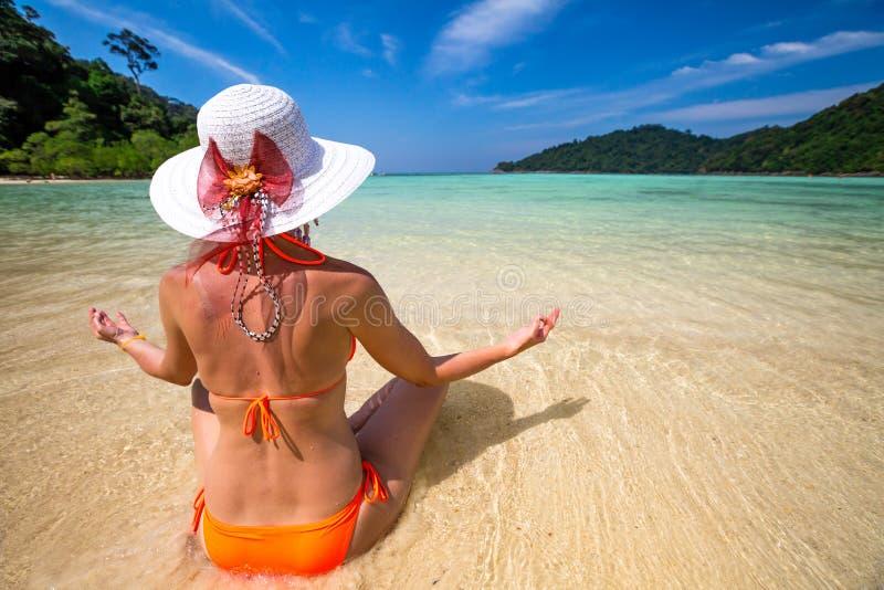 Mulher que meditating na praia