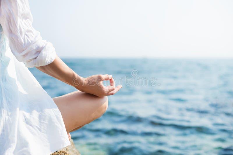 Mulher que meditating no mar imagem de stock