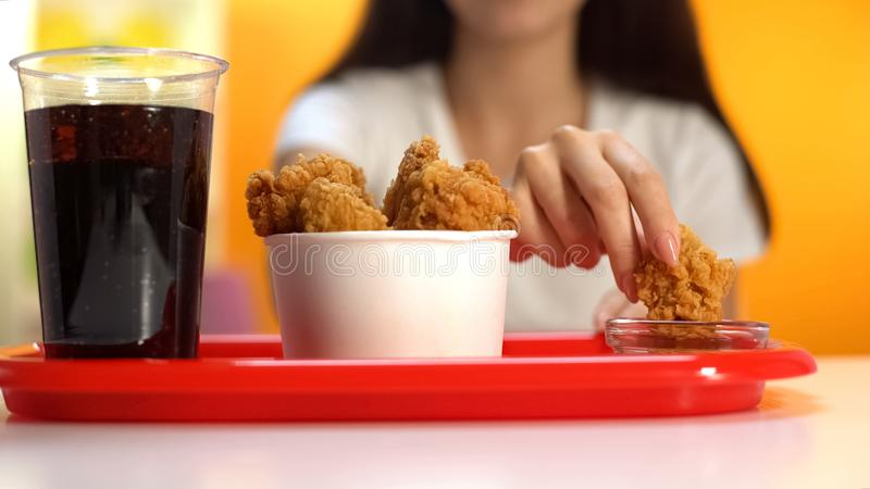 Mulher que mergulha as asas de frango frito fri?veis no close up do molho da ketchup, petisco crocante fotos de stock royalty free