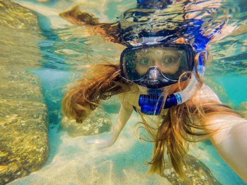 Mulher que mergulha em águas tropicais na frente da ilha exótica imagem de stock royalty free