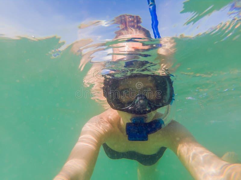Mulher que mergulha em águas tropicais na frente da ilha exótica fotos de stock royalty free