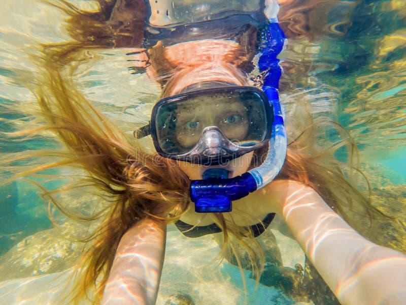 Mulher que mergulha em águas tropicais na frente da ilha exótica fotografia de stock royalty free