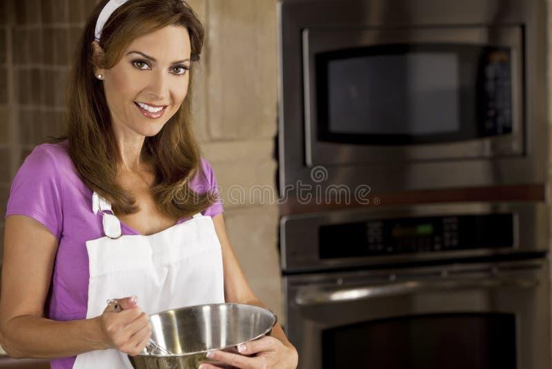Mulher que mistura e que coze na cozinha fotografia de stock