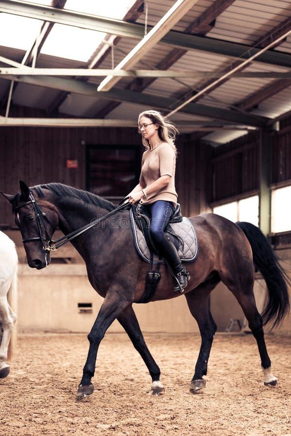 Mulher que monta seu cavalo imagens de stock royalty free