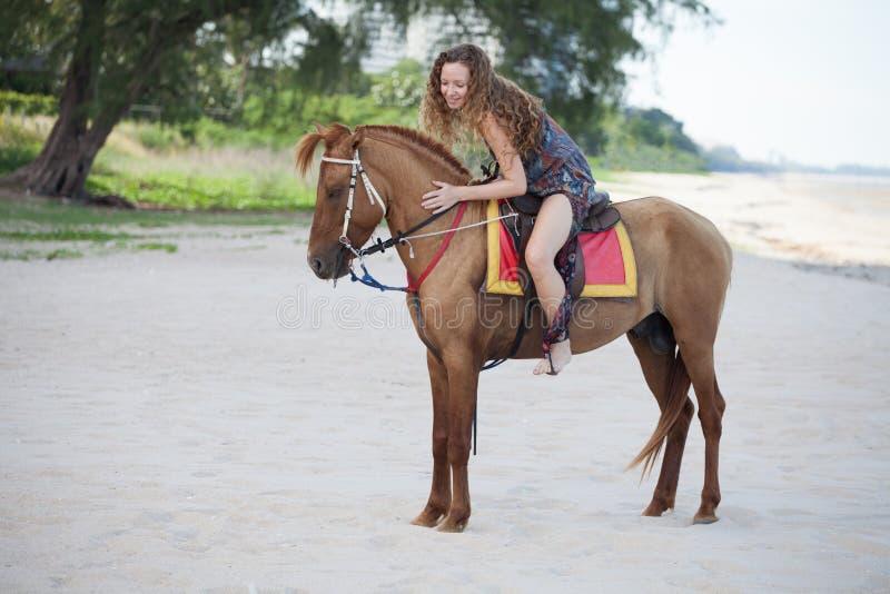 Mulher que monta um cavalo na praia da areia nas horas de verão foto de stock