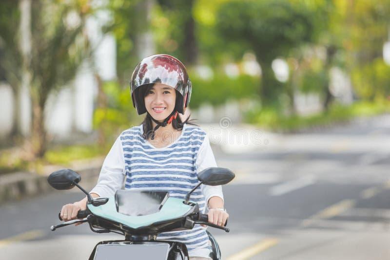 Mulher que monta um motorcyle ou um velomotor imagens de stock royalty free