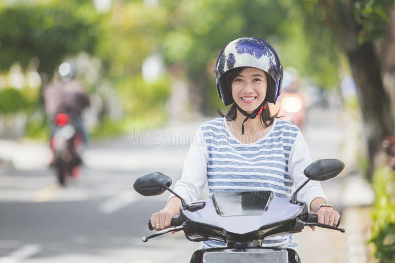 Mulher que monta um motorcyle ou um velomotor foto de stock royalty free