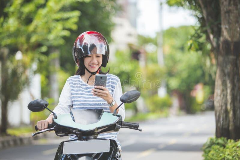 Mulher que monta um motorcyle ou um velomotor fotografia de stock