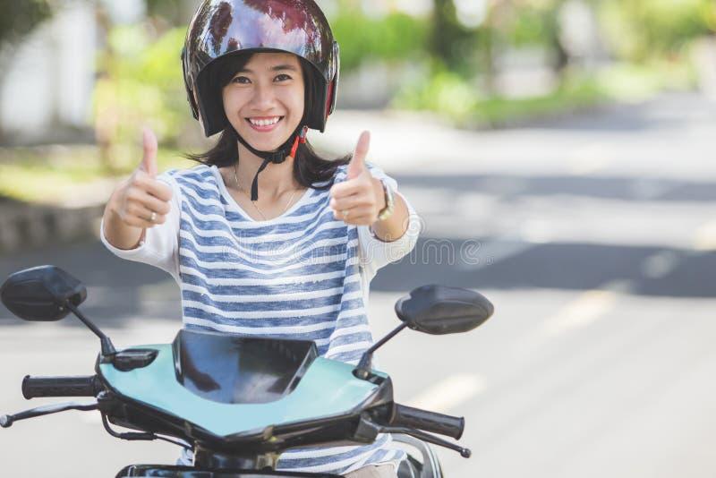Mulher que monta um motorcyle ou um velomotor foto de stock