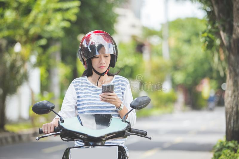 Mulher que monta um motorcyle ou um velomotor imagens de stock