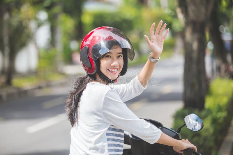 Mulher que monta um velomotor e que acena a mão imagens de stock royalty free