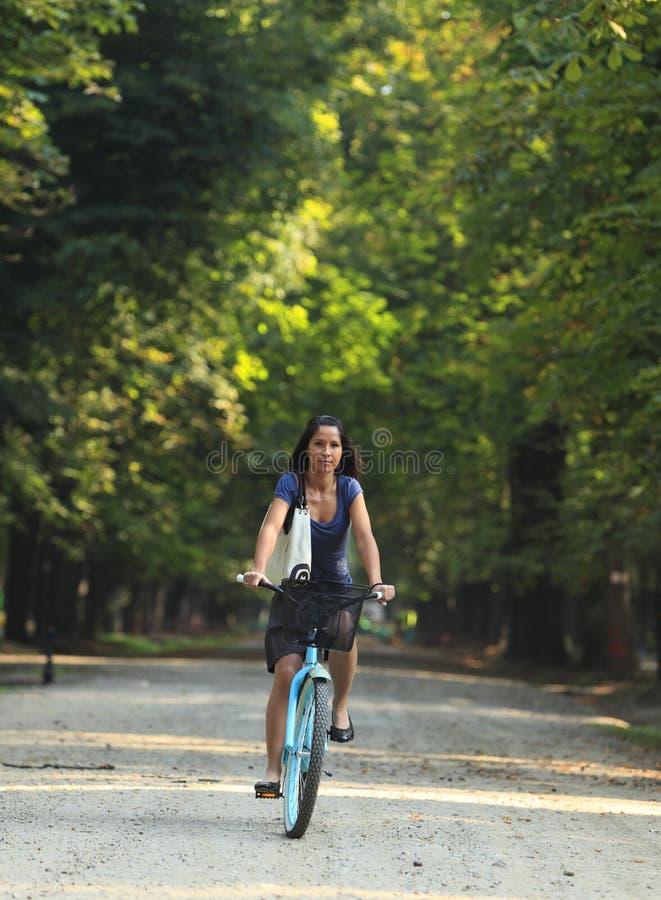 Mulher que monta uma bicicleta foto de stock royalty free