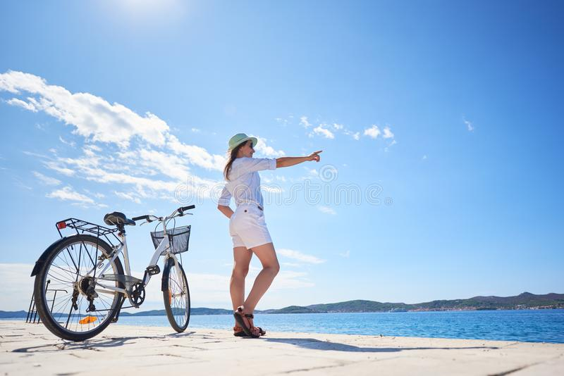 Mulher que monta uma bicicleta ao longo do passeio rochoso na água do mar efervescente azul foto de stock royalty free