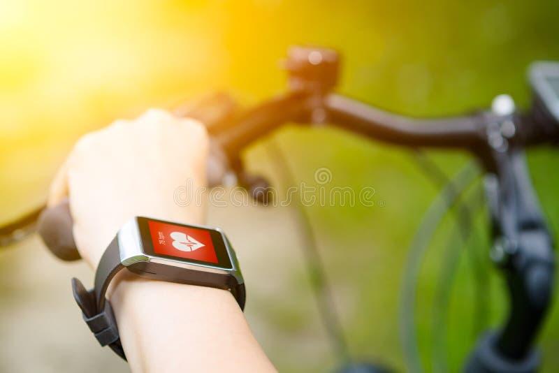 Mulher que monta uma bicicleta com um monitor da frequência cardíaca do smartwatch imagem de stock royalty free