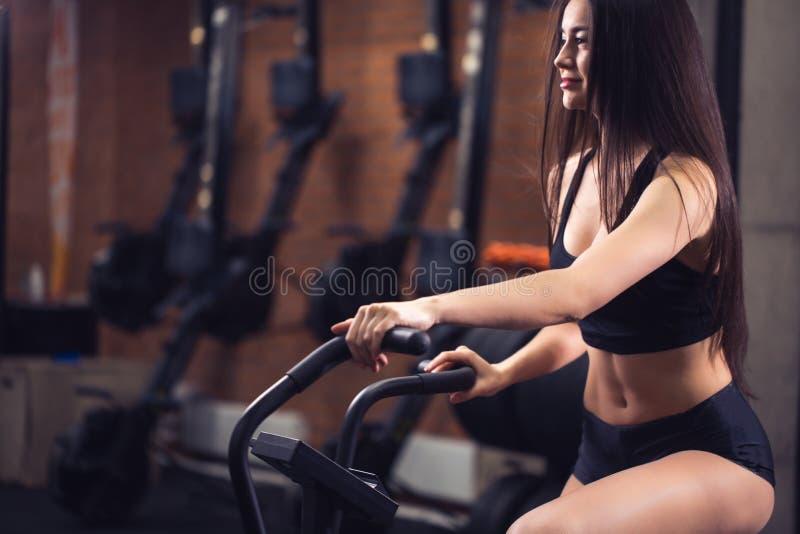 Mulher que monta uma bicicleta de exercício no gym menina apta que faz o cardio- treinamento na bicicleta imagens de stock