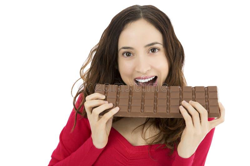 Mulher que morde uma barra de chocolate grande imagem de stock