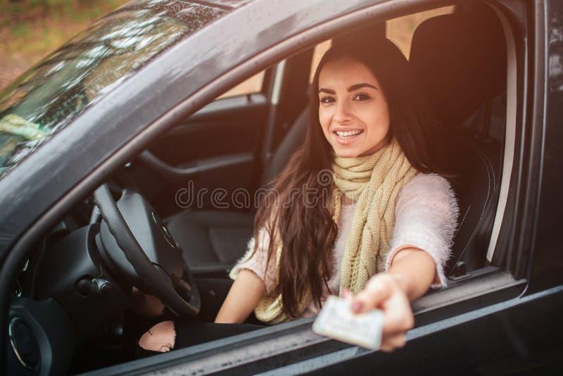 Mulher que mostra a carteira de motorista Feche acima da mão Conceito do outono Viagem da floresta do outono pelo carro foto de stock royalty free