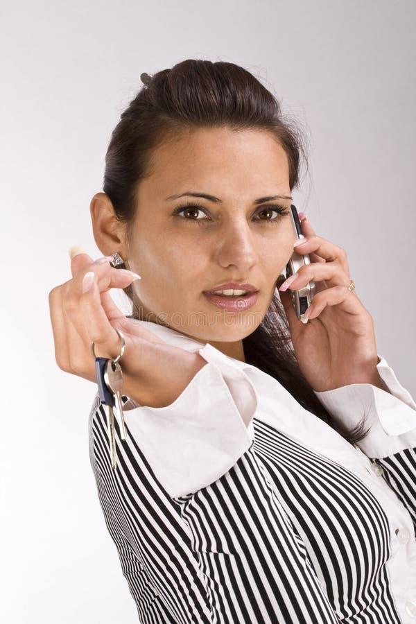 Mulher que mostra a chave fotografia de stock