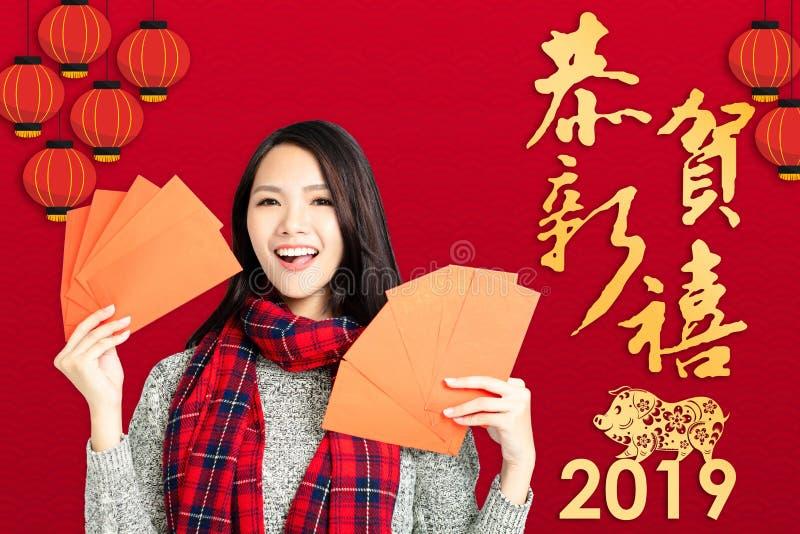 mulher que mostra envelopes vermelhos pelo ano novo chinês T chinês imagem de stock royalty free