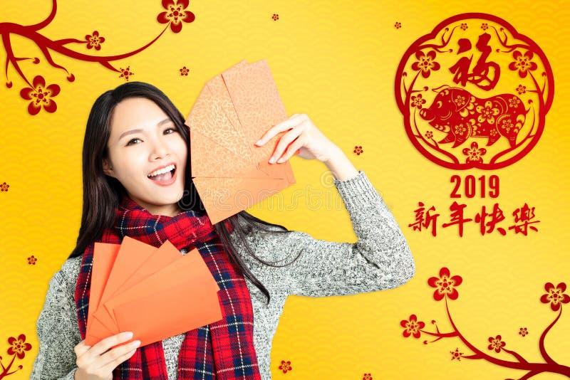 mulher que mostra envelopes vermelhos pelo ano novo chinês T chinês imagens de stock