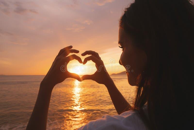 Mulher que mostra a forma de um coração com mãos no por do sol sobre o mar, curso da jovem mulher foto de stock royalty free