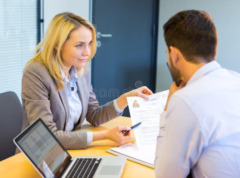 Mulher que mostra o cv a um empregador no escritório imagens de stock
