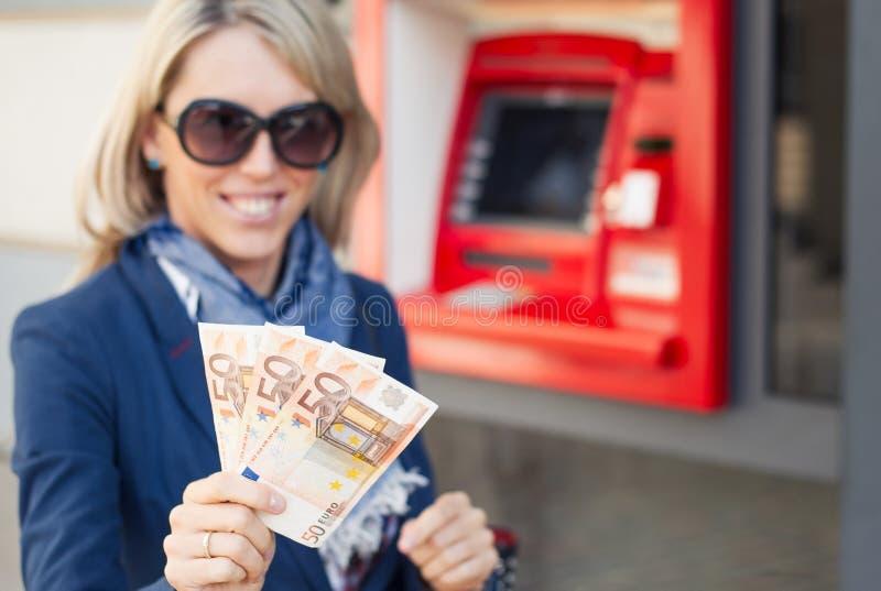 Mulher que mostra o dinheiro após a retirada do ATM foto de stock