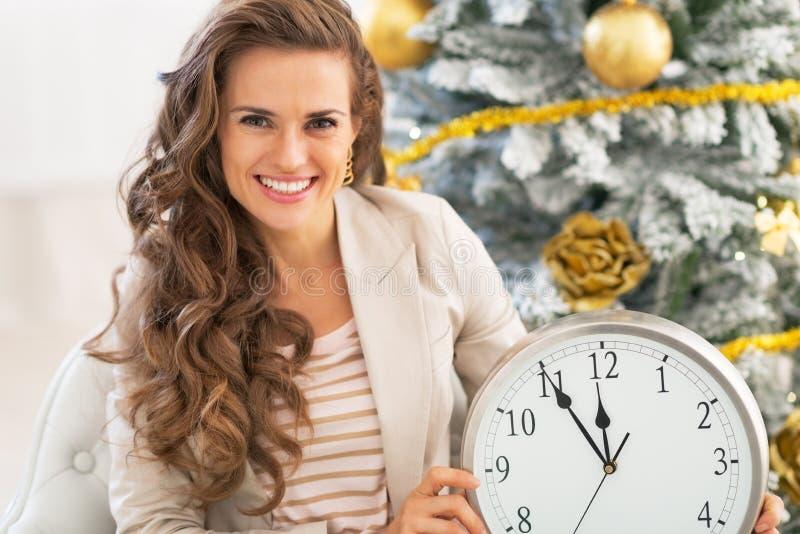 Mulher que mostra o pulso de disparo perto da árvore de Natal fotografia de stock