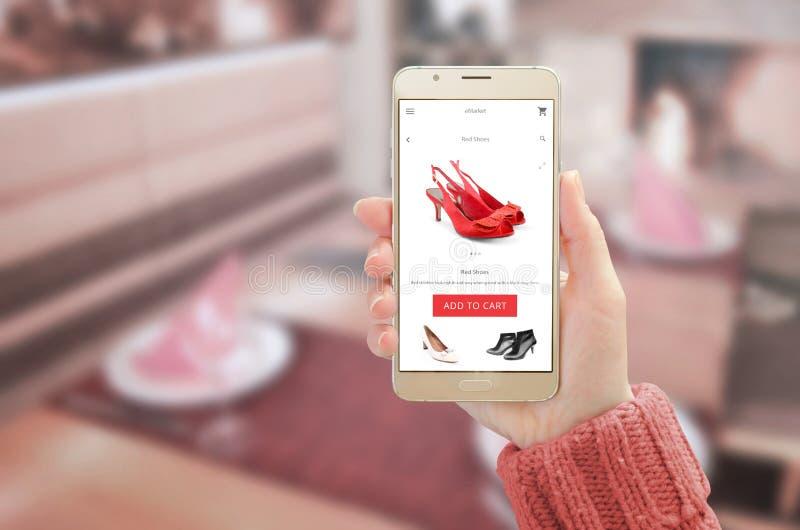 Mulher que mostra a ouro moderno o telefone esperto com app de compra em linha na exposição do dispositivo fotografia de stock royalty free