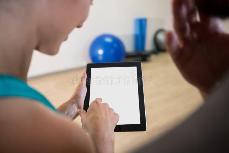 Mulher que mostra a tabuleta digital ao instrutor da aptidão foto de stock