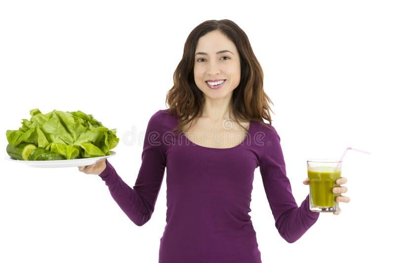 Mulher que mostra um vidro do batido verde e de vegetais verdes imagens de stock