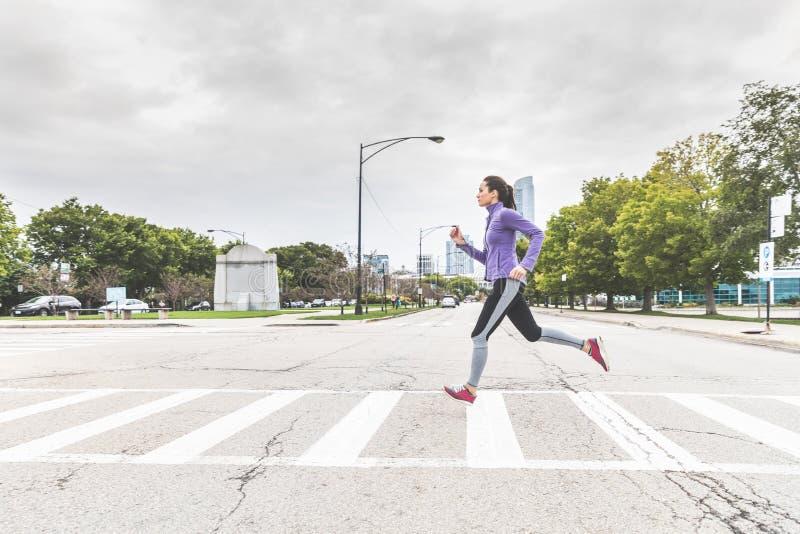 Mulher que movimenta e que cruza a estrada na zebra em Chicago foto de stock royalty free