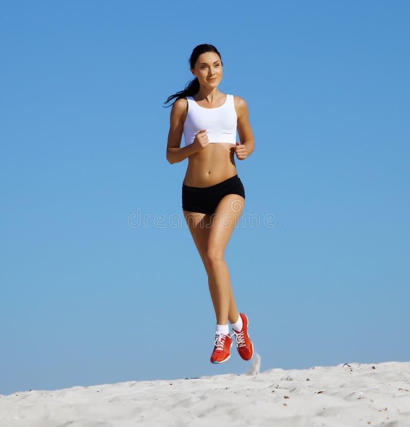 Mulher que movimenta-se na areia fotografia de stock royalty free