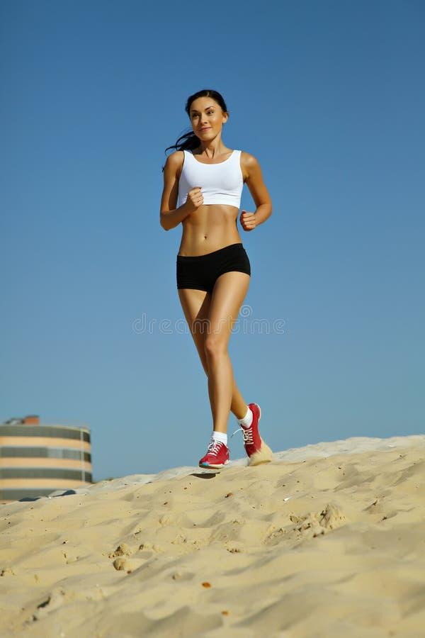 Mulher que movimenta-se na areia imagens de stock