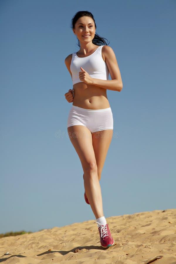 Mulher que movimenta-se na areia imagem de stock