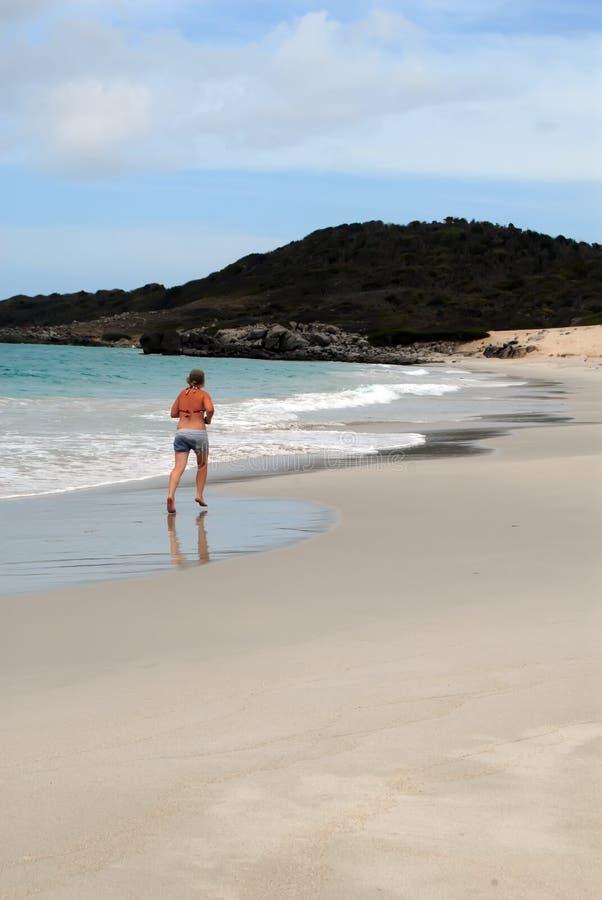 Mulher que movimenta-se na praia branca fotografia de stock