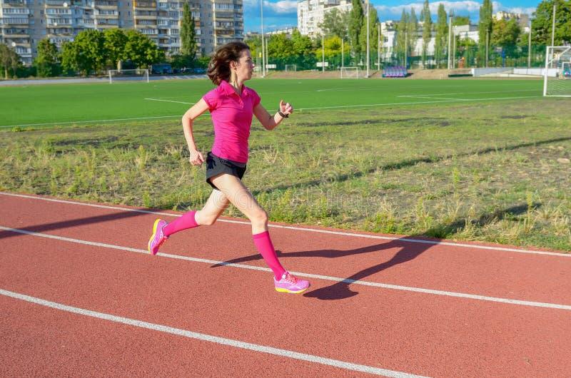 Mulher que movimenta-se na trilha, correndo no estádio fotos de stock