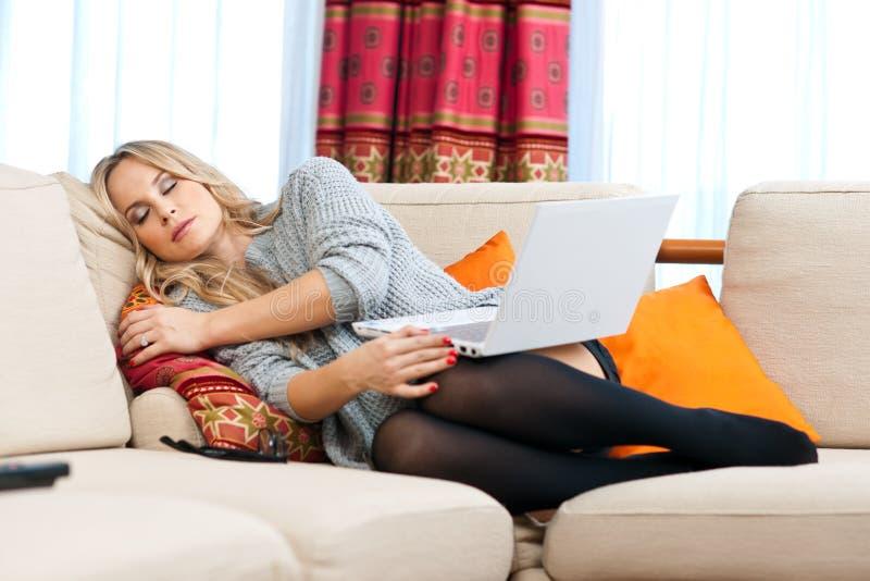 Mulher que napping em seu sofá imagens de stock