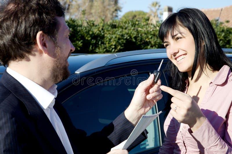 Mulher que obtém chaves do carro novo do vendedor fotos de stock royalty free