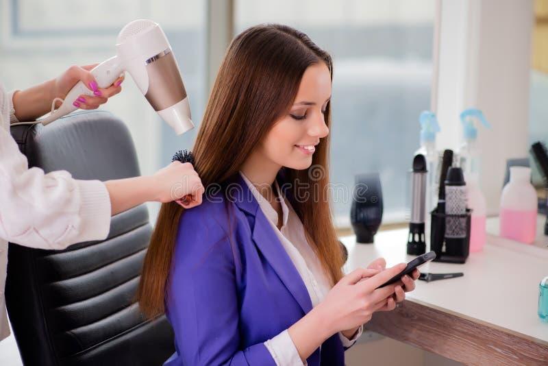 A mulher que obtém lhe o cabelo feito na loja de beleza imagens de stock royalty free