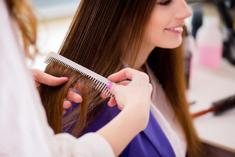 A mulher que obtém lhe o cabelo feito na loja de beleza foto de stock