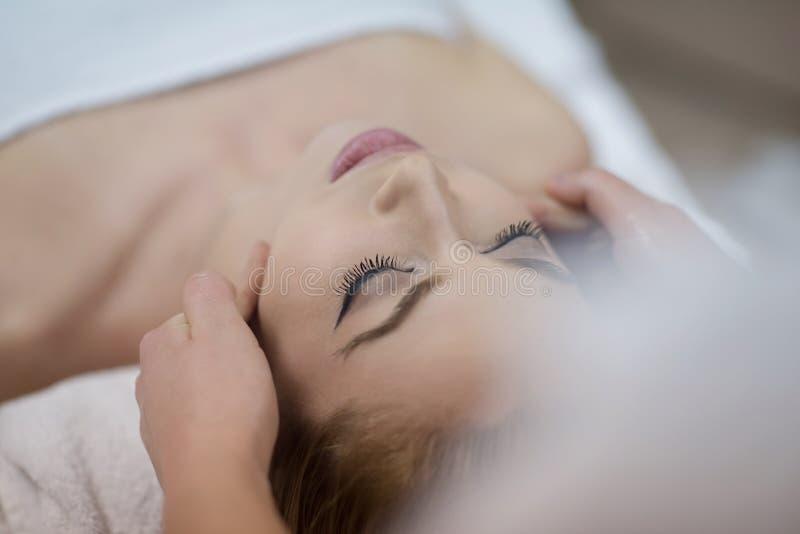 Mulher que obtém a massagem da cara e da cabeça no salão de beleza dos termas imagem de stock
