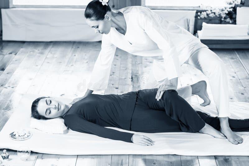 Mulher que obtém a massagem de esticão tailandesa tradicional pelo terapeuta fotos de stock