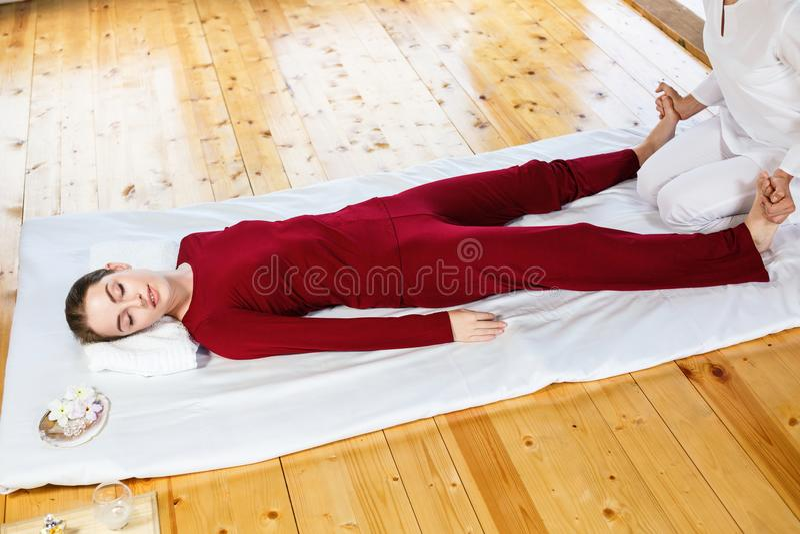 Mulher que obtém a massagem de esticão tailandesa tradicional pelo terapeuta foto de stock