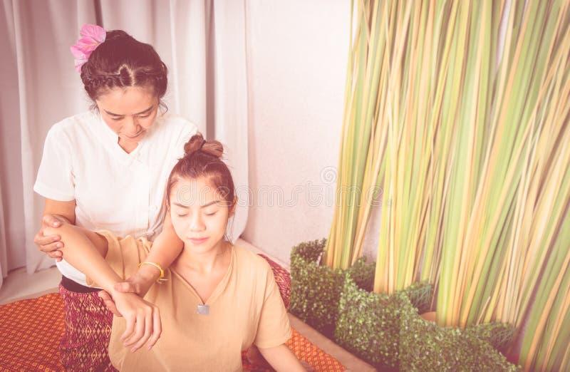 Mulher que obtém a massagem do braço em termas tailandeses da massagem fotografia de stock royalty free
