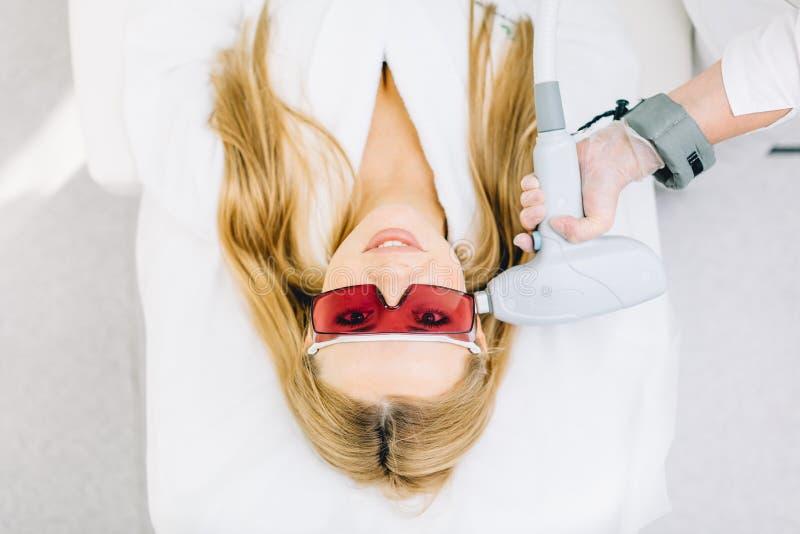Mulher que obtém o laser e o tratamento da cara do ultrassom no centro médico dos termas fotos de stock