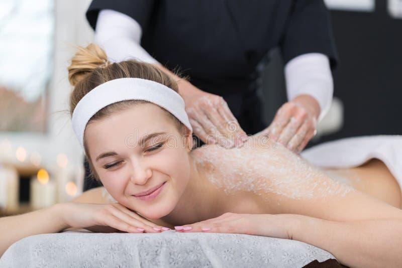A mulher que obtém o sal exfoliating esfrega a massagem no ` s do esteticista fotografia de stock