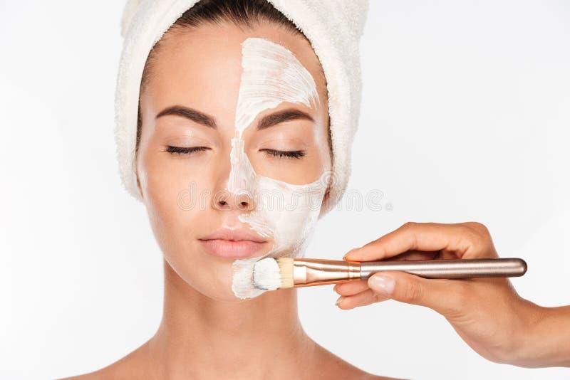 Mulher que obtém o tratamento da máscara da pele da beleza na cara com escova imagem de stock