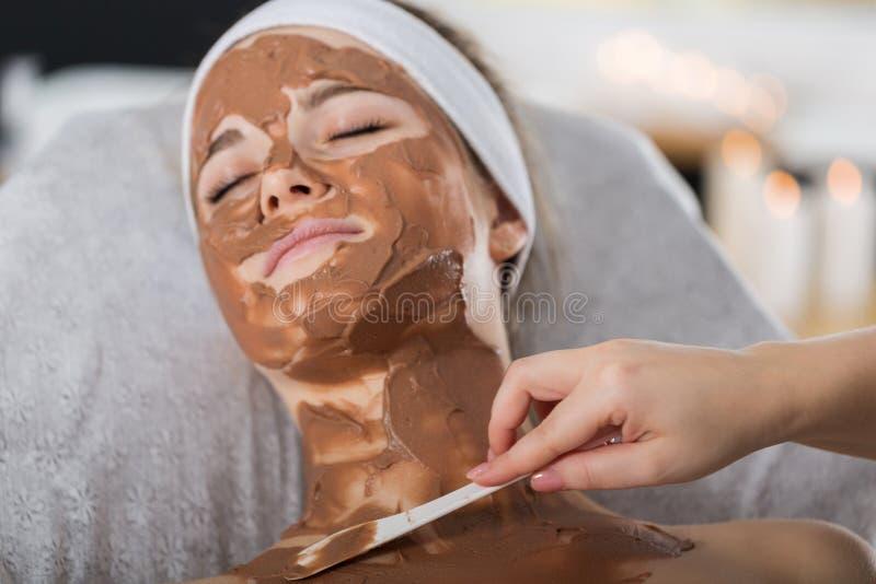 Mulher que obtém o tratamento da máscara do chocolate nos termas imagens de stock