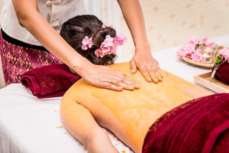 A mulher que obtém a pele traseira esfrega com sal alaranjado em termas tailandeses fotografia de stock